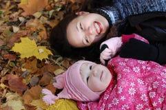 Mum met een dochter in de herfstpark stock fotografie