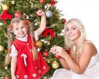 Mum met een dochter verfraait Kerstmisboom. Stock Foto