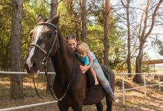 Mum met zoonsaandrijving op paard Stock Foto's