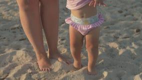 Mum och att behandla som ett barn dottern som har stor tid på stranden arkivfilmer