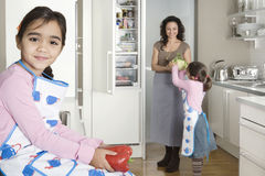 Mum och döttrar i kök Arkivfoto