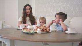 Mum och farsa som sammanfogar deras gossebarn p? kaf?tabellen lager videofilmer