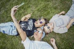 Mum och söner som ligger på gräs och gör selfies lycklig begreppsfamilj arkivfoton