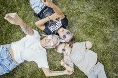 Mum och söner som ligger på grönt gräs ovanför sikt lycklig begreppsfamilj arkivfoton