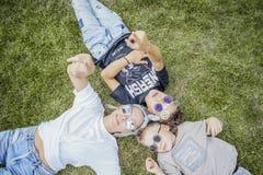 Mum och söner som ligger på grönt gräs ovanför sikt lycklig begreppsfamilj royaltyfria bilder