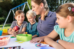Mum painting pictures with their children and during lunch break Royalty Free Stock Photography