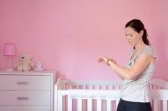 Mum patrzeje jej zegarek podczas gdy jej dziecko śpi obraz stock