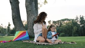 Mum play with a small daughter. Mum play with a small daughter on a green lawn in the park stock video