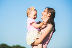 Mum playing with child outside on sunny warm day stock image