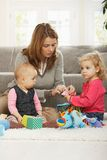 Mum playing with two daughters. Mum playing on floor with two baby daughters at home Stock Photo