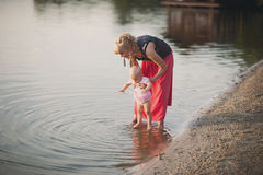 Mum plays with the small daughter near water. Childhood, love, life style Royalty Free Stock Images