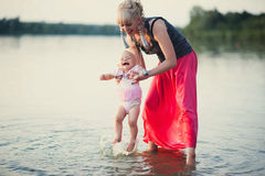 Mum plays with the small daughter near water. Childhood, love, life style Stock Image