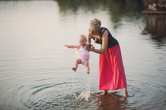 Mum plays with the small daughter near water. Childhood, love, life style Stock Images