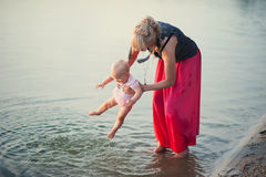 Mum plays with the small daughter near water. Childhood, love, life style Royalty Free Stock Photography