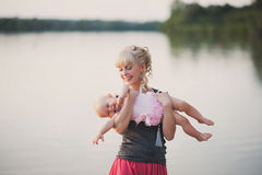 Mum plays with the small daughter near water. Childhood, love, life style Stock Photos