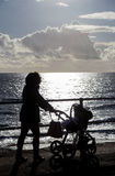 Mum with pram walking along sea front silhouettte Royalty Free Stock Images