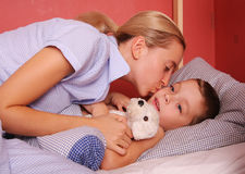 Mum puts to bed a sonny. 2 stock photo