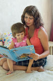 Mum reads the book. Mum reads to a small daughter the book royalty free stock photo