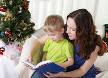 Mum reads to the son the book stock images