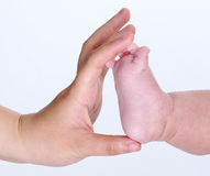 Mum's hand holding baby's little foot Stock Photos