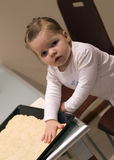 Mum's helper. A cute little girl helping her mother in the kitchen, playing with pastry (dough) at the kitchen table Stock Photos