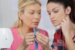 Mum showing daughter how to fix zipper. Mum showing daughter how to fix a zipper Stock Photography