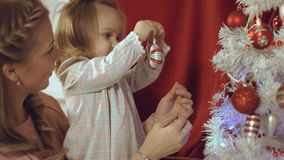 Mum with a small daughter decorate a Christmas tree Royalty Free Stock Image