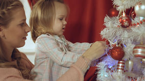 Mum with a small daughter decorate a Christmas tree Stock Image