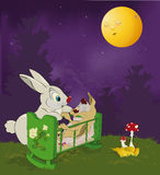 Mum and small rabbit. Rabbit mum swinging a rabbit in wood and under the moon Stock Photo