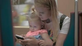 Mum som använder mobiltelefonen under gångtunnelritt med den lilla dottern arkivfilmer