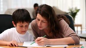 Mum som gör läxa med hennes son lager videofilmer