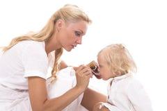 Mum som ger en sked av sirap till liten flicka Arkivbild
