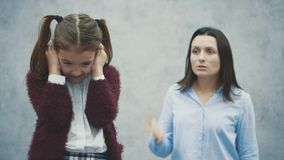 Mum som skriker på hennes dotter, som står bak hennes moder Begreppet av uppfostran är inte en organiserad dotter arkivfilmer