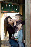 Mum and son. Mum caringly wipes her son's nose in a playground stock photos
