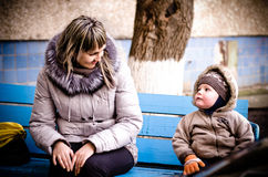 Mum and the son on a bench in a court yard. Look against each other in the autumn Stock Photo