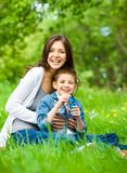 Mum and son with book in park Stock Image