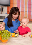 Mum with son eat fruit Royalty Free Stock Photos