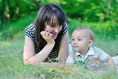 Mum and the son lie on a grass. Family on a grass. Mum looks at the son. The son looks afar Royalty Free Stock Image