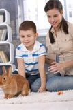 Mum and son with pet rabbit at home Stock Images