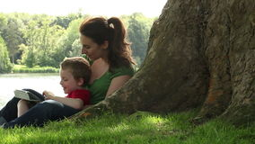 Mum and son playing under a tree. Mum and son playing with a tablet under a tree in the park stock video footage