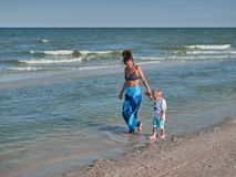 Mum and son are walking along the beach. Young mother with kid little boy are on the seaside. Happy family and happy stock images