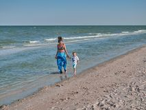 Mum and son are walking along the beach. Young mother with kid little boy are on the seaside. Happy family and happy stock photo