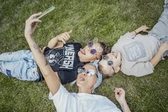 Mum and sons lying on grass and making selfies. Happy family concept. stock photos