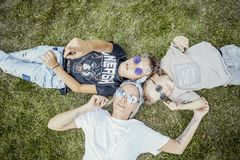 Mum and sons lying on green grass. View from above. Happy family concept. royalty free stock image