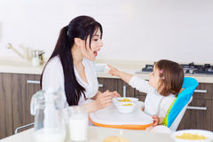 Mum spoon feeding child in kitchen.Family Royalty Free Stock Images