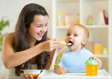 Mum spoon feeding child son Stock Image