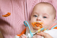 Mum spoon-feeds the child. With smashed pumpkin Royalty Free Stock Photo