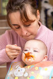 Mum spoon-feeds the child. With smashed pumpkin Stock Photography