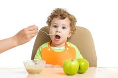Mum spoon-feeds the child Royalty Free Stock Photo
