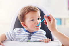 Mum spoon-feeds the child Stock Image